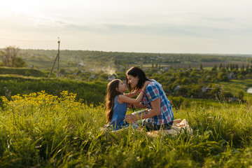 Little cute girl with her mother sitting at sunset