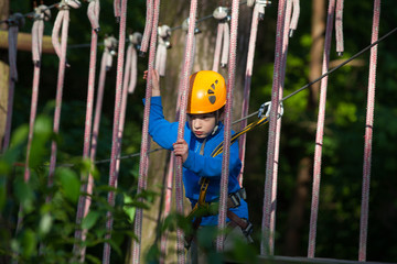 boy  climbing in adventure park,  rope park