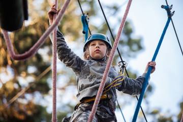 Girl climbing in adventure park , rope park
