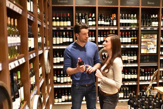 junges Paar berät über Weinkauf im Markt