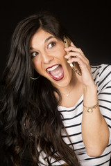 Excited beautiful brunette woman talking on her cell phone
