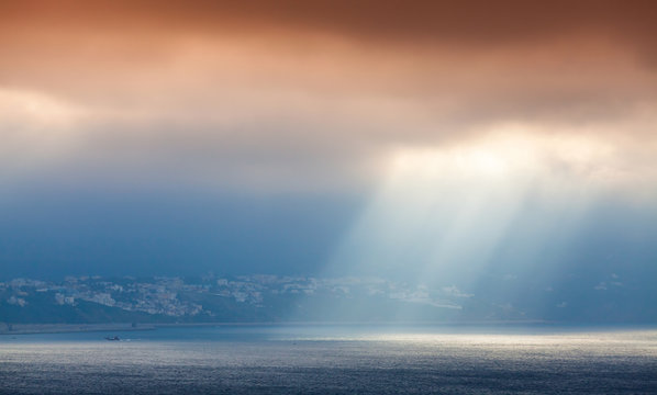 Sunlight goes through clouds. Bay of Tangier