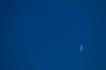 The moon in the blue sky.