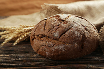Freshly baked bread on brown wooden background