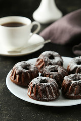 Chocolate bundt cakes on plate on black background