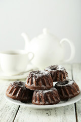 Chocolate bundt cakes on plate on white wooden background