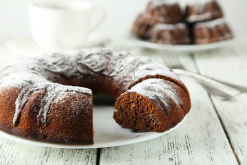 Chocolate bundt cake on plate on white wooden background