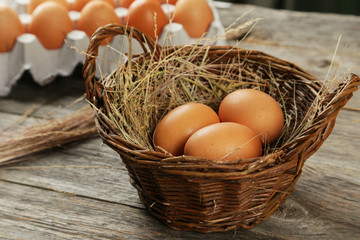 Eggs in basket on brown wooden background