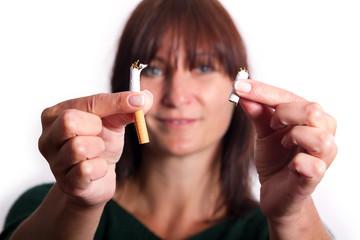 lächelnde Frau zerbricht eine Zigarette in der Hälfte