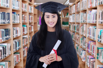 Graduate student holding a diploma in library