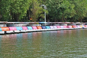 Many pedal boats with running number arrange in lake.