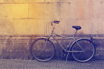 Vintage bicycle over stone wall. Retro filter effect