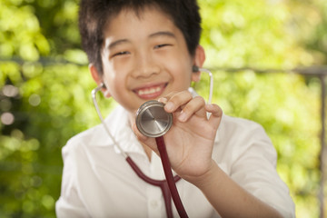 Asian young boy having stethoscope playing doctor
