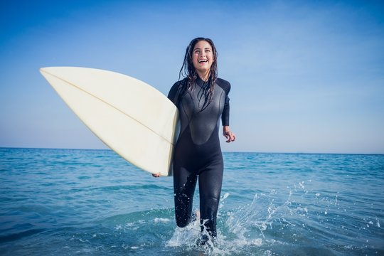 woman in wetsuit with a surfboard on a sunny day
