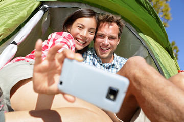 Camping couple in tent taking selfie smartphone