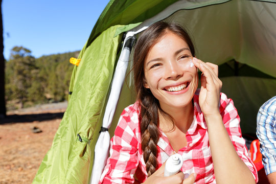 Camping woman applying sunscreen sun cream in tent