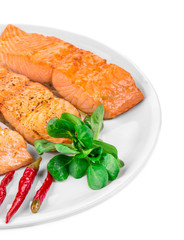 Grilled salmon fillet with vegetables on plate.