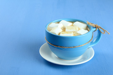 A cup of hot chocolate with marshmallows on the wooden background