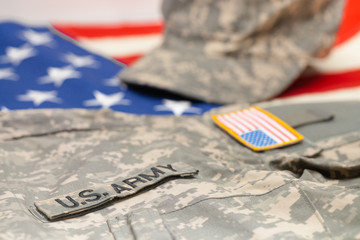 USA army uniform lying over national flag - studio shot