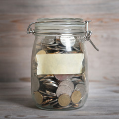 Coins in glass money jar with blank label