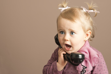 Baby girl in surprise talking on a vintage phone