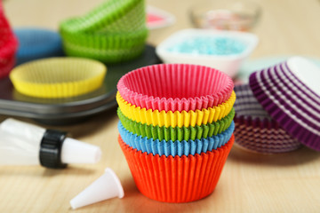 Empty colorful cupcake cases on wooden background