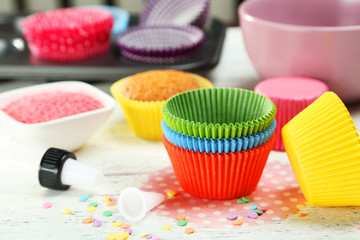 Empty colorful cupcake cases on white wooden background