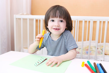 Cute little boy paints with felt pens