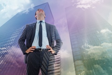 Composite image of happy businessman with hands on hips