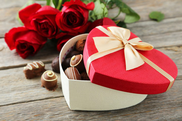 Beautiful heart gift box with chocolates on grey wooden backgrou