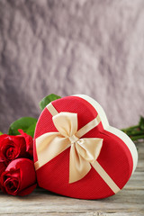 Beautiful heart gift box on grey wooden background