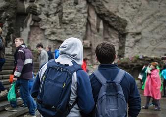 Два путешественника, смотрящие на имена погибших