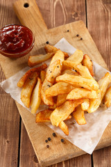 Fried Potatoes on old wooden cutting board with bowl ketchup.