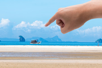 Finger pointing at a picture beach. Dream concept
