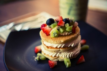 Pancakes, fruit, kiwi, strawberry berry sauce and strawberry.