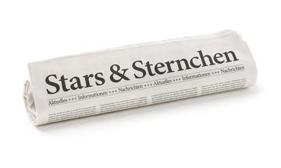 Zeitungsrolle mit der Überschrift Stars und Sternchen