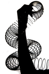 silhouette of hands holding a slinky