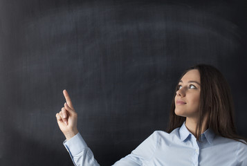 Businesswomen pointing to blank blackboard
