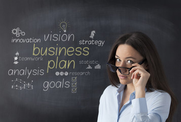 Businesswoman in front of blackboard with business strategy plan