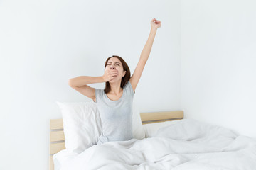 Asian woman yawning at the morning in living room