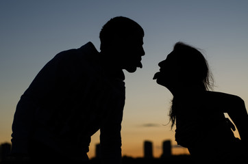 Young couple showing each other tongue against the evening city