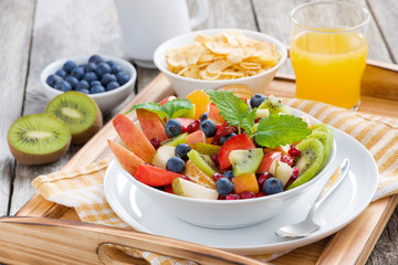 breakfast with fruit salad, cornflakes and orange juice