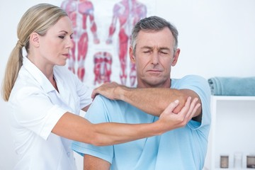 Doctor stretching a man arm