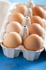 Eggs in the package on blue wooden table