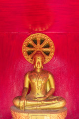 the sitting gold buddha statue  with the red color background