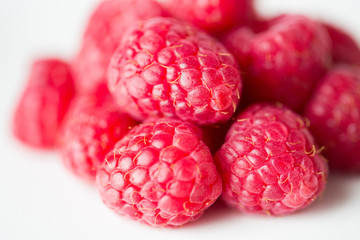 juicy fresh ripe red raspberries on white
