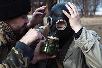 A friend helps his buddy to take on the gas mask for the mission