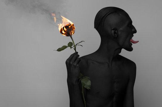 a man with black skin holding a burning rose, black death