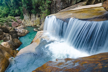 Jungle waterfall with flowing water, large rocks
