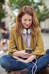 junge frau sitzt draußen mit handy und kopfhörern